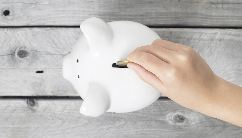 Asian boy hand dropping a coin into white piggy bank  against wooden grey background